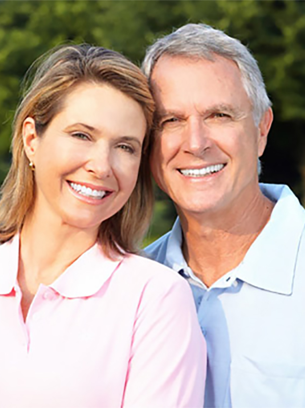 A senior couple smiling for a photo in a park