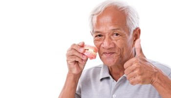 A senior man holding his new dentures