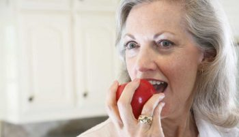 A senior woman biting into an apple