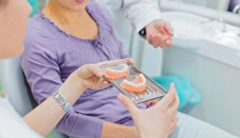 A woman is shown her new dentures at the denture clinic