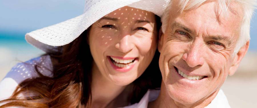 A couple wearing flexible partial dentures at the beach
