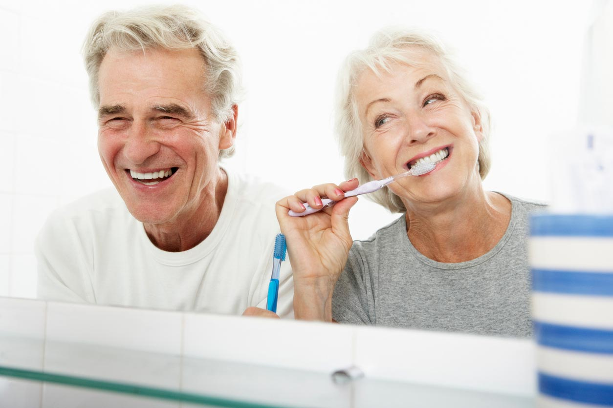 A senior couple smiling and cleaning their teeth