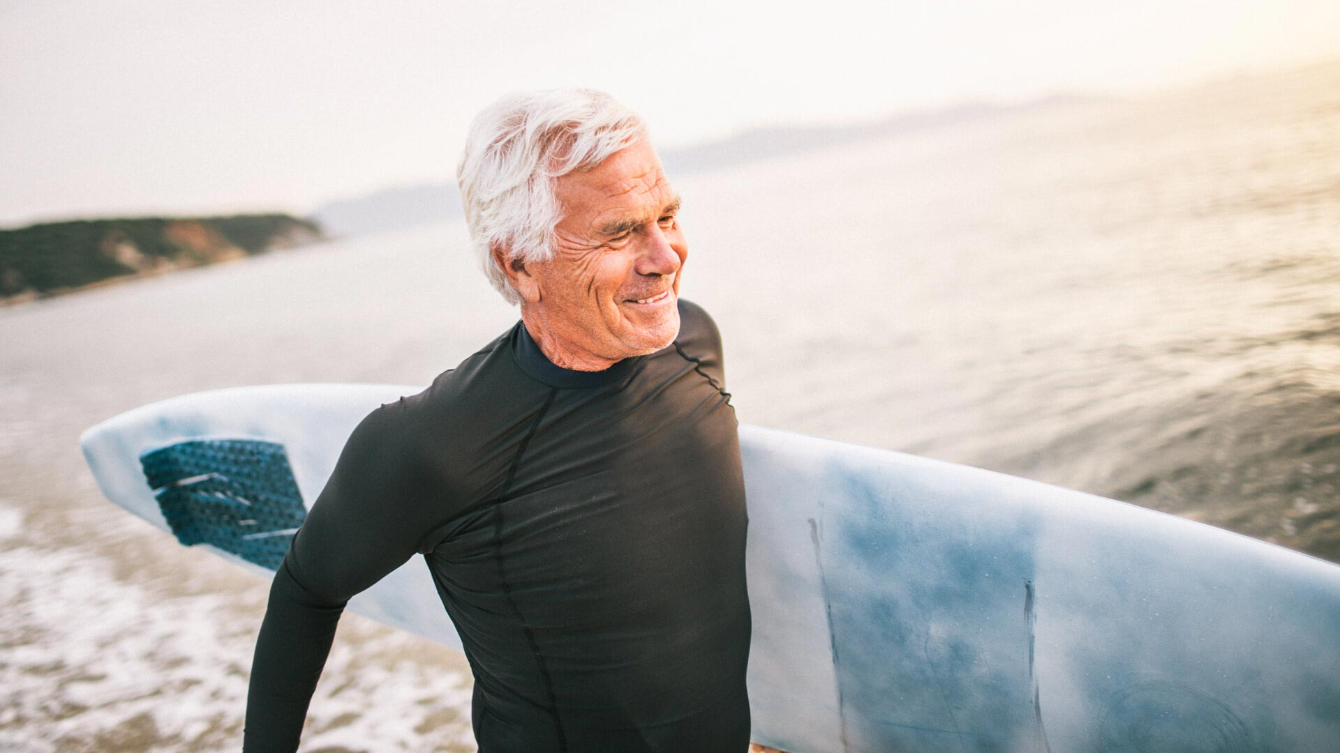 A senior man going surfing at the beach